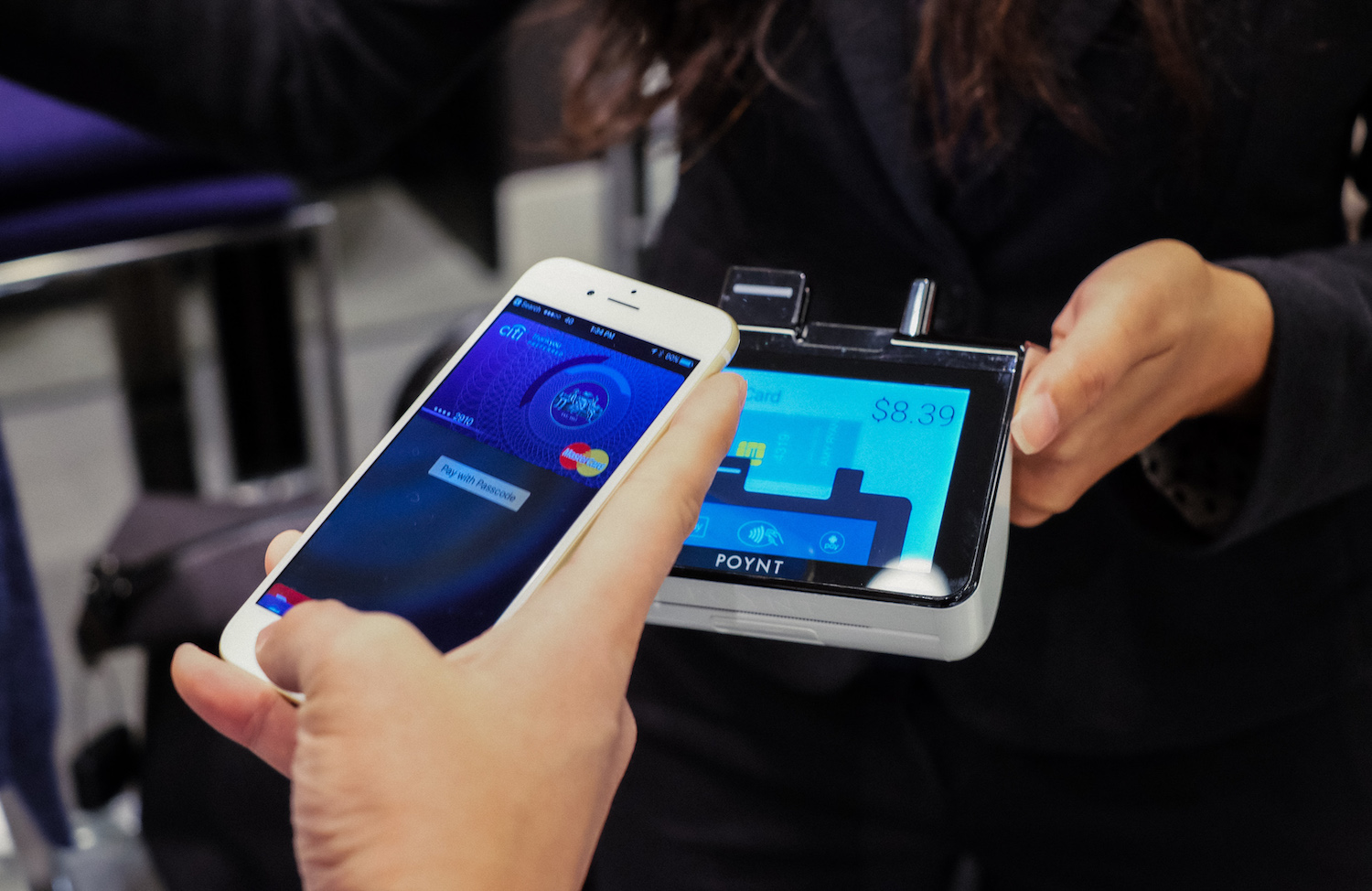 Image of a poynt terminal and a person with a payment on phone